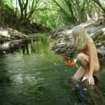 nudist lady kneeling in the river, hidden river, nudist resort, nudie blues, weekend resort